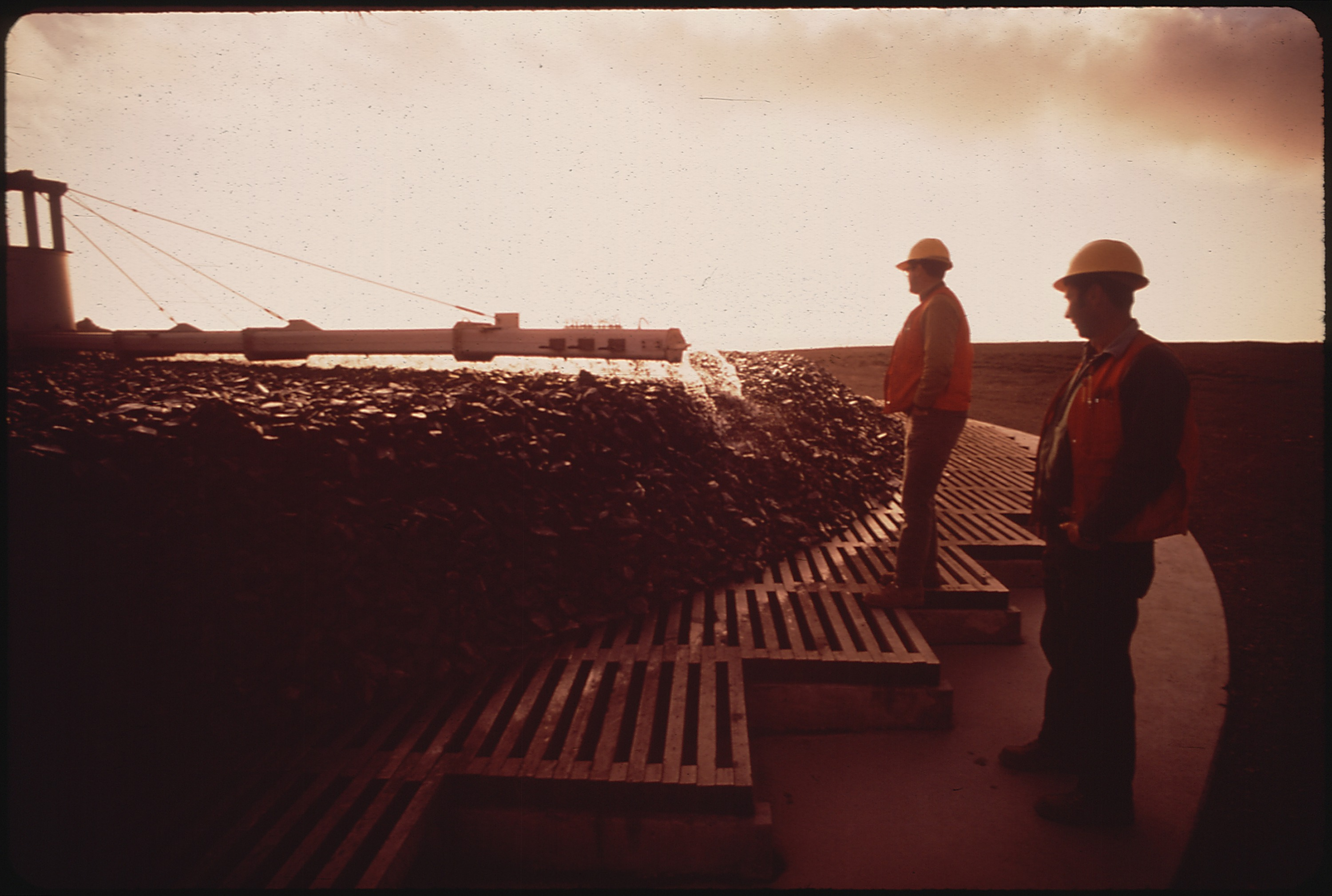 SEWAGE_TREATMENT_PLANT_AT_SUNSET._TWO_WORKERS_STAND_NEAR_ROCK_FILTER_-_NARA_-_542989