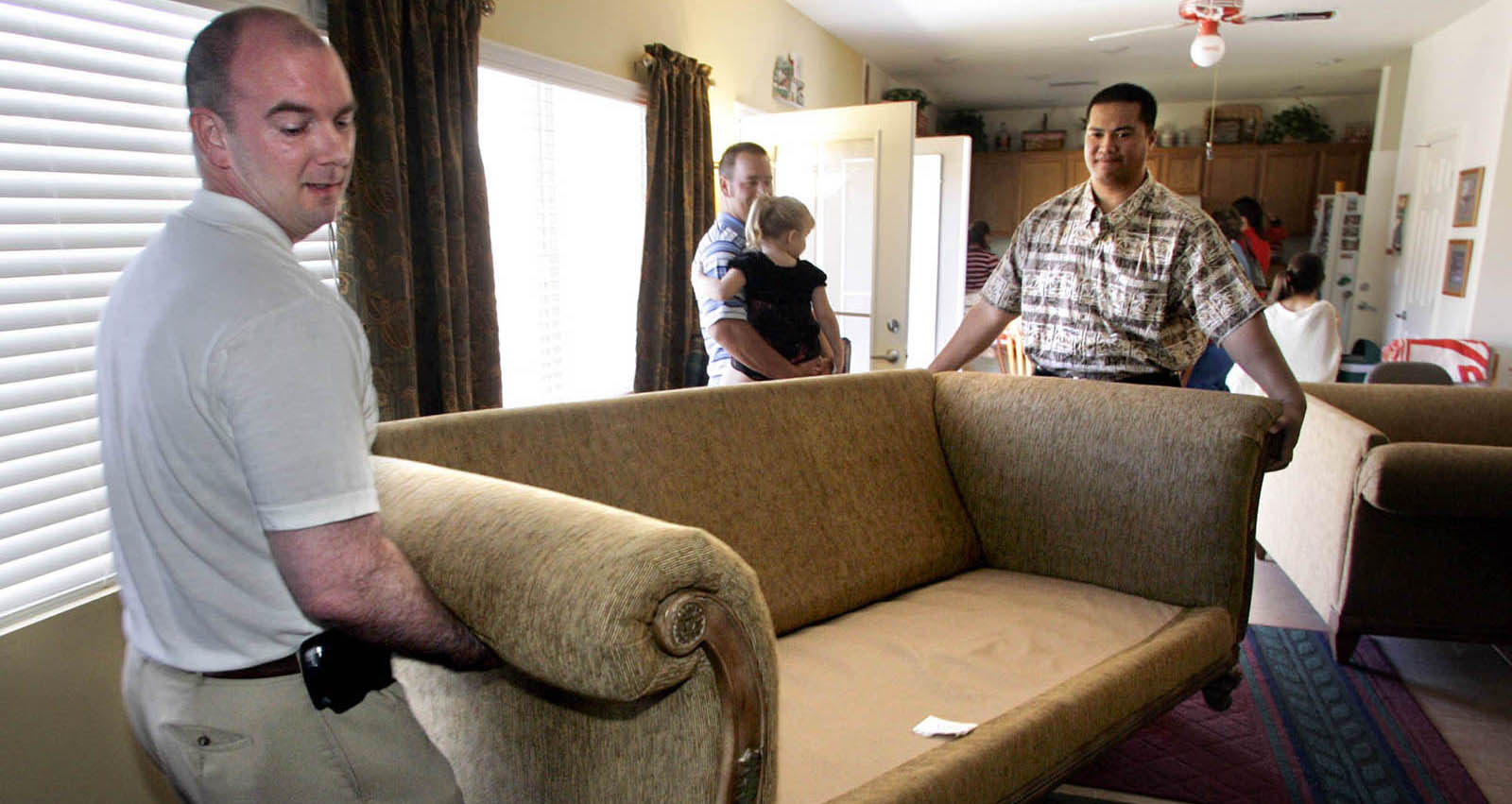 Discovery Church members Kirk Butler, left, and Vili Fetapai move furniture back into a living room after a Sunday service at their pastor's home January 23, 2005. The church is waiting for approval to move to a temporary industrial location. STEVE MARCUS / LAS VEGAS SUN