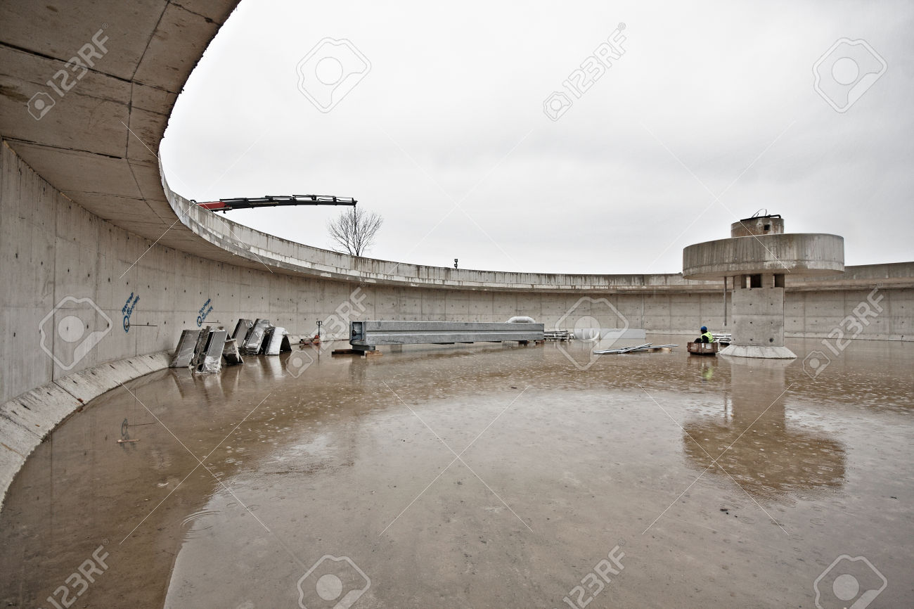Huge concrete circular sedimentation tank Water settling, purification in the water station. Man sitting under the pillar. As an umbrella